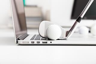 Golf ball resting on a laptop that represents the start of your relationship with your marketing agency